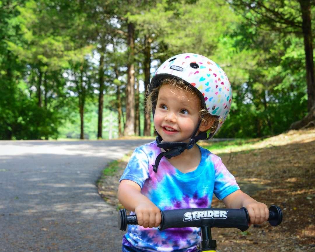 dívka v růžové a bílé helmě jedoucí na kole na silnici - dívka v růžové a bílé helmě jedoucí na kole na silnici během dne (8×7)