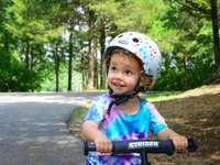 dívka v růžové a bílé helmě jedoucí na kole na silnici
