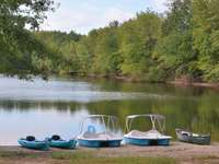синя и бяла лодка на езерото през деня