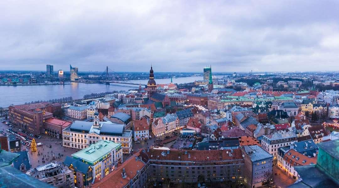 vista aérea de edifícios da cidade durante o dia - Vista da cidade da Igreja de São Pedro  A plataforma de observação da igreja oferece uma vista panorâmica da cidade de Riga com o rio Daugava. Riga, Letônia (7×4)