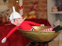 bebeluș în pălărie roșu și alb de Moș Crăciun pe castron de lemn maro
