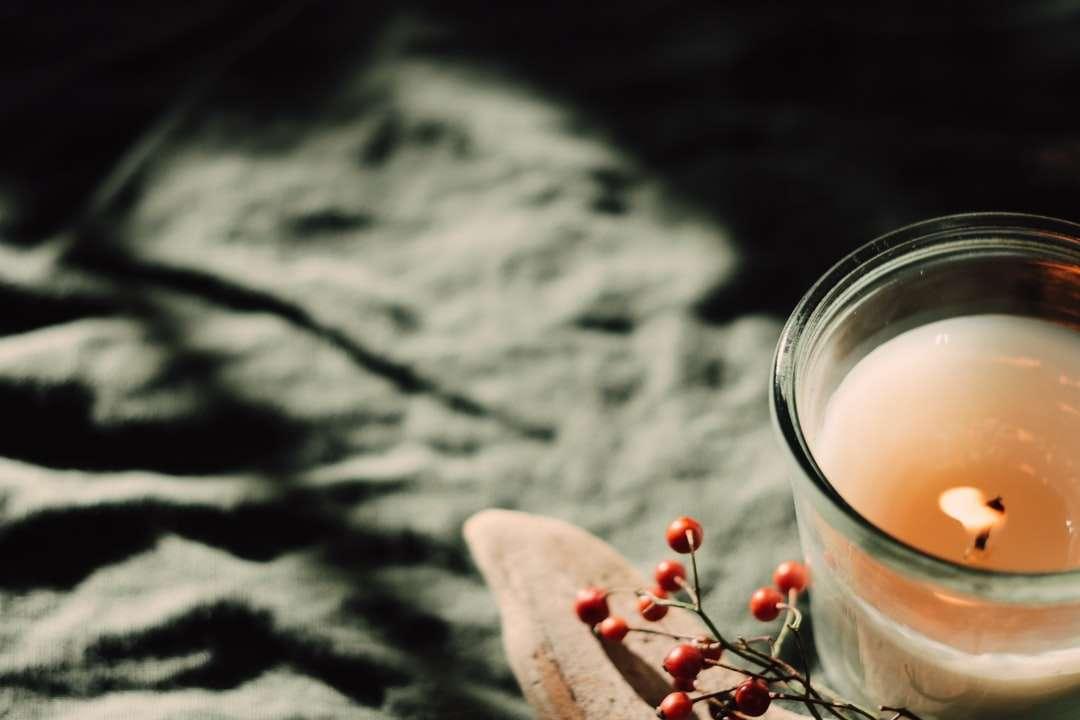 Verre à boire clair avec un liquide blanc sur une table en bois marron - Bougie et feuillage (13×9)