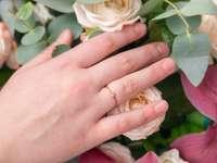 person som bär guldbröllop som håller vit ros