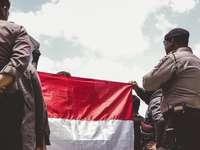 férfi fekete kabátot, fehér és piros zászlót tartó