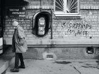 man i grå jacka som står nära väggen med graffiti