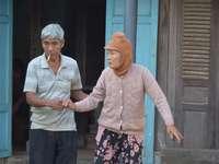 homem de camisa azul em pé ao lado da mulher