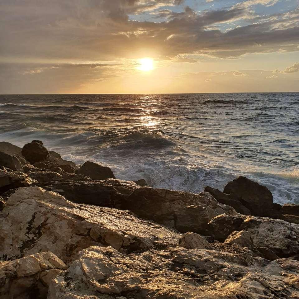 costa rocciosa grigia durante il tramonto - Tramonto sulla spiaggia (19×19)