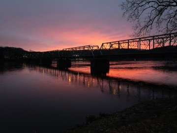silueta mostu přes vodu při západu slunce