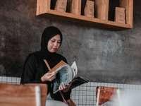 kobieta w czarnym hidżabie trzymając biały kubek ceramiczny