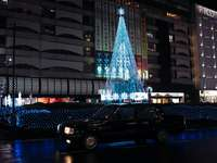 czarny sedan zaparkowany w pobliżu oświetlonej choinki