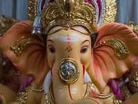 zlatá a fialová figurka hinduistického božstva