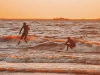 2 Männer und Frau, die Hände am Strand während des Sonnenuntergangs halten