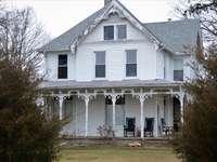 бяла и сива дървена къща близо до зелени дървета през деня