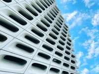wit betonnen gebouw onder de blauwe hemel overdag