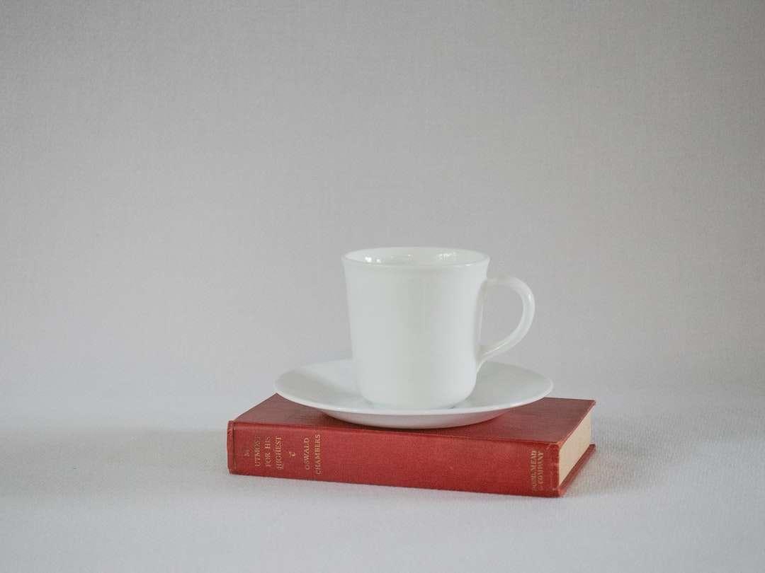 witte ceramische mok op rood boek