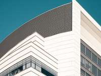 bílá betonová budova pod modrou oblohou během dne