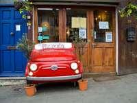 Volkswagen T-2 van rouge garée à côté d'un bâtiment en bois brun