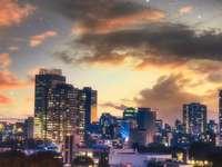 panoramę miasta pod zachmurzonym niebem w porze nocnej