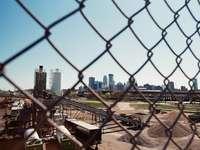 szare metalowe ogrodzenie w pobliżu budynków miejskich w ciągu dnia