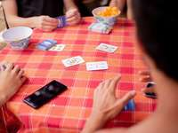 person holding playing cards on table