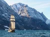barco marrom e branco no mar perto da montanha durante o dia