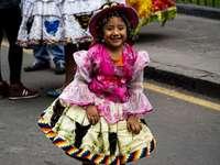ragazza in abito floreale rosa e bianco che indossa cappello tessuto marrone