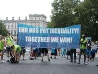 Leute, die auf Straße mit blauem und weißem Banner gehen