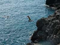 man in green shorts jumping on rocky cliff by the sea