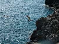άντρας σε καταπράσινα σορτς πηδώντας σε βραχώδη βράχο δίπλα στη θάλασσα