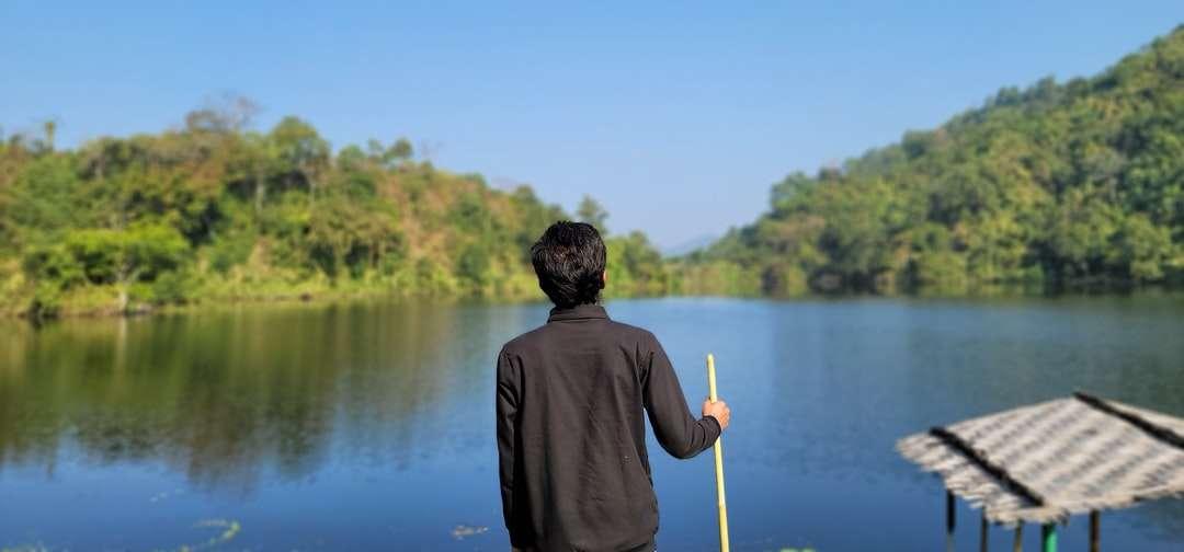 Homme en sweat à capuche gris tenant un bâton jaune près du lac - homme en sweat à capuche gris tenant un bâton jaune près du lac pendant la journée. Une vallée verte naturelle accrocheuse. Lac Boga, Bandarban, Bangladesh (6×3)