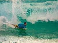 άντρας σε μπλε πουκάμισο σερφάρισμα στα κύματα της θάλασσας κατά τη διάρκεια της ημέρας