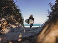 pessoa de jaqueta preta em pé na estrada de terra marrom