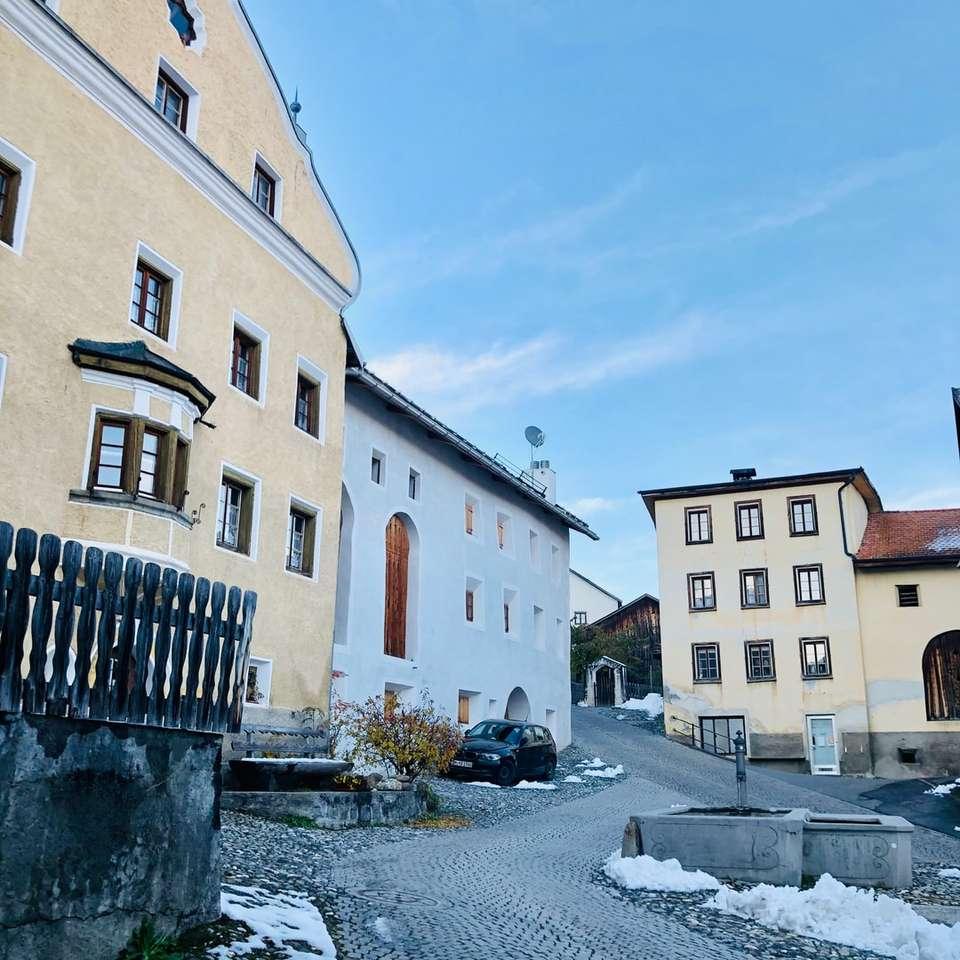 коли, паркирани до бяла бетонна сграда през деня - Малкото селце Цхлин в кантон Граубън, Швейцария, се счита за най-красивото село в целия регион Енгадин. Tschlin, 755 (13×13)