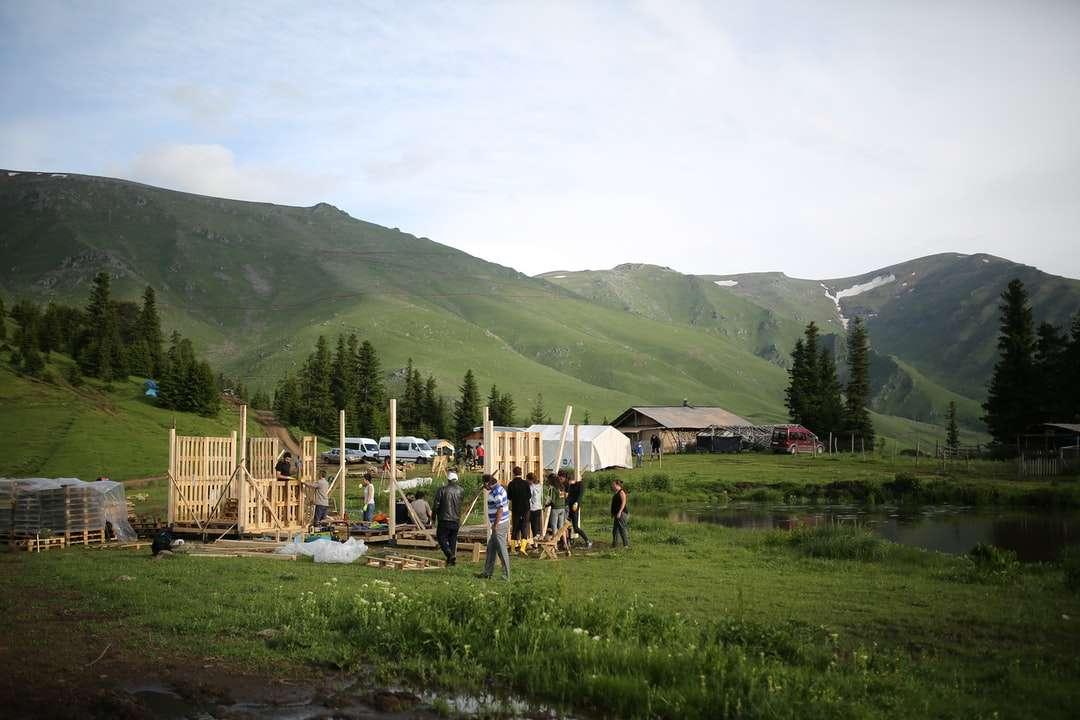 gente de pie en el campo de hierba verde cerca de montañas verdes - personas de pie en el campo de hierba verde cerca de montañas verdes durante el día (12×8)