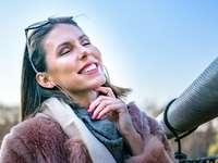 mujer sonriente en abrigo de piel marrón