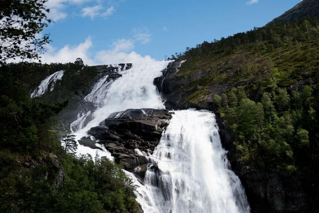 vattenfall på stenigt berg under blå himmel under dagtid - Vattenfall på bergfloden i sommar. Norge (7×5)