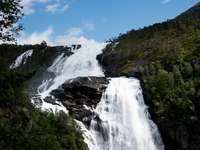 водопади на скалиста планина под синьо небе през деня