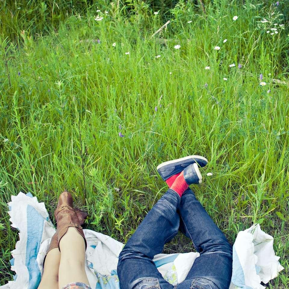 kobieta w niebieskich dżinsach leżącego na białej tkaninie - kobieta w niebieskich dżinsach leżących na białej tkaninie na polu zielonej trawie w ciągu dnia. Ludzie r. W polu trawy na kocu (9×9)