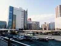 автомобили, паркирани на паркинг в близост до високи сгради