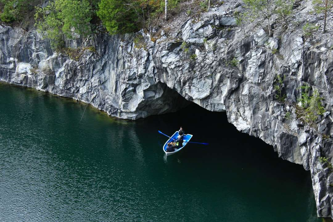 Mann im blauen Kajak auf Fluss nahe grauem felsigem Berg - Mann im blauen Kajak auf Fluss nahe grauem felsigem Berg während des Tages. Boot, Wasser, Felsen, Ruskeala, Karelien, Marmor (12×8)