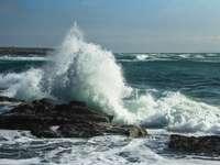 vlny oceánu narážející na hnědý skalní útvar během dne