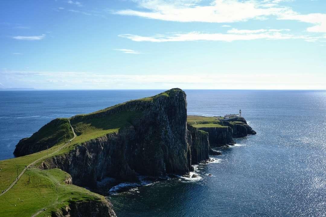 formação de rocha verde e preta ao lado do mar sob o céu azul - formação de rocha verde e preta ao lado do mar, sob o céu azul durante o dia (15×10)