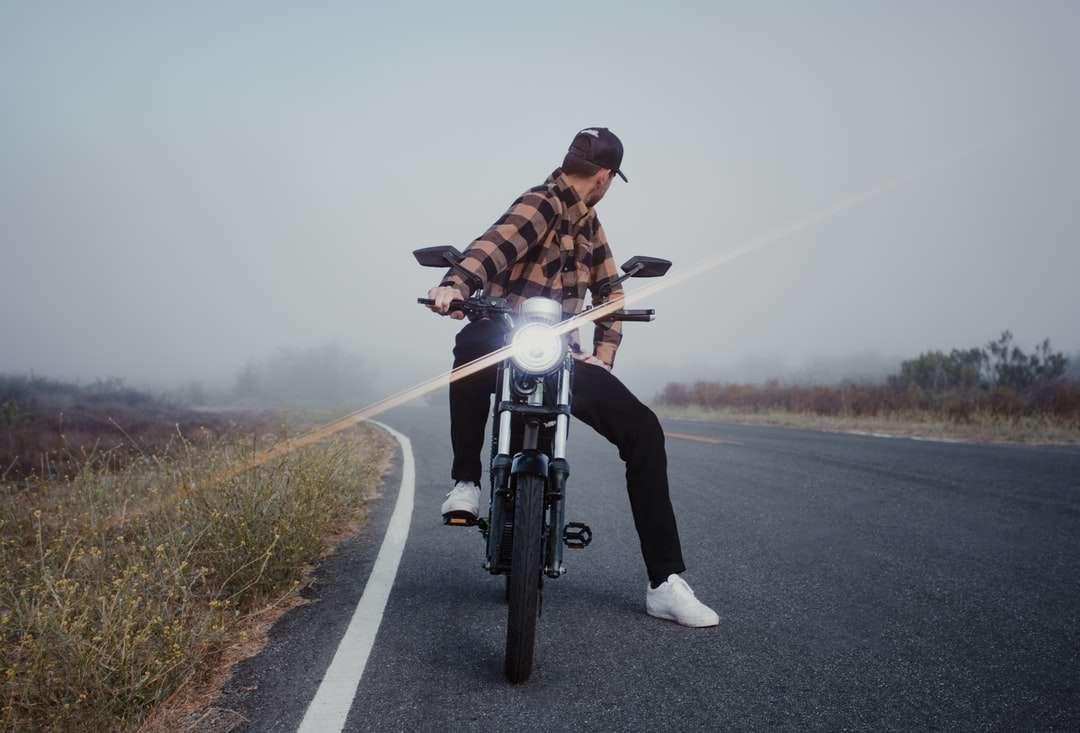 homem de jaqueta marrom andando de bicicleta na estrada durante o dia - Modelo alto, verificando se há carros que se aproximam em sua bicicleta elétrica durante um amanhecer nublado (7×5)
