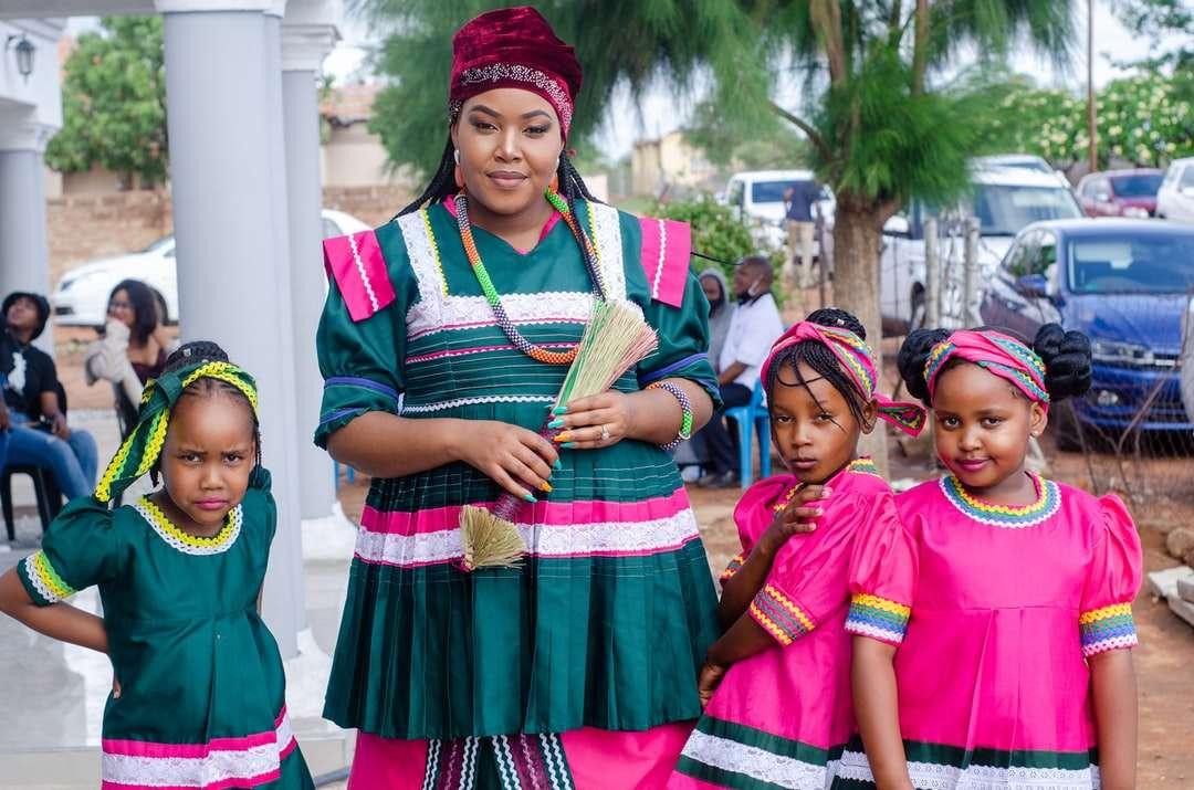 γυναίκα με πράσινο και κόκκινο φόρεμα που στέκεται δίπλα στο κορίτσι - γυναίκα σε πράσινο και κόκκινο φόρεμα που στέκεται δίπλα στο κορίτσι σε ροζ φόρεμα. . Bochum, Limpopo, Νότια Αφρική (19×13)