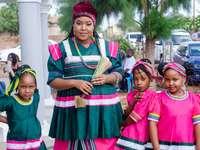 γυναίκα με πράσινο και κόκκινο φόρεμα που στέκεται δίπλα στο κορίτσι