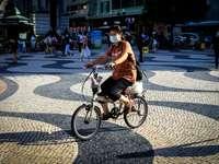 γυναίκα σε καφέ πουκάμισο ιππασία σε ποδήλατο στο δρόμο