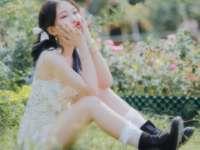Frau im weißen Blumenkleid, das auf grünem Grasfeld sitzt