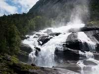 El agua cae sobre la montaña rocosa bajo un cielo azul durante el día
