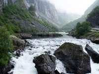 река между зелени планини през деня
