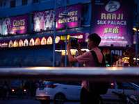 muž v bílém triku s fotografii obchodu během noční doby